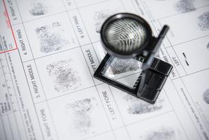 Loupe over fingerprints on arrest formの写真素材 [FYI03498619]
