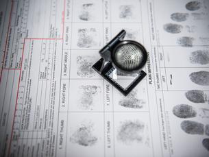 Loupe over fingerprints on arrest formの写真素材 [FYI03498621]