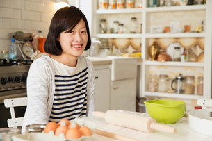 Portrait of young woman at kitchen table with baking ingrediの写真素材 [FYI03498955]