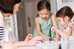 Mother and young daughters making pastryの写真素材 [FYI03498959]