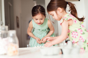 Two young sisters making pastryの写真素材 [FYI03498964]