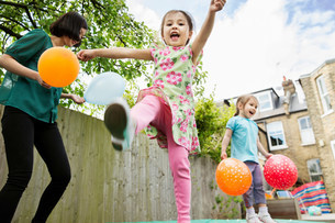 Mother and daughters playing in garden with balloonsの写真素材 [FYI03498974]