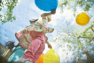Young girls bouncing on garden trampoline with balloonsの写真素材 [FYI03498981]