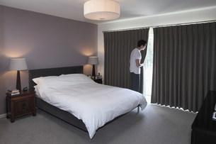 Man peeping behind bedroom curtainの写真素材 [FYI03499126]