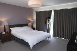 Woman peeping behind bedroom curtainの写真素材 [FYI03499128]