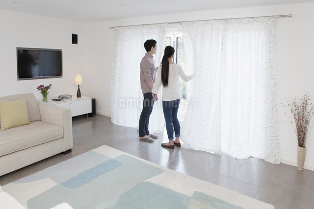Husband and wife looking out of glass doorの写真素材 [FYI03499146]