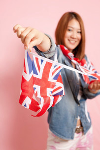 Young woman holding Union flag bunting, portraitの写真素材 [FYI03499240]