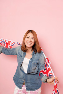 Young woman holding Union flag bunting, portraitの写真素材 [FYI03499242]