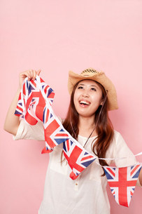 Young woman holding Union flag bunting, smilingの写真素材 [FYI03499249]