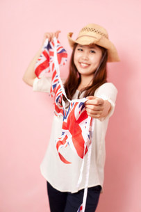 Young woman holding Union flag bunting, smilingの写真素材 [FYI03499251]