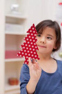 Girl holding Christmas tree decorationの写真素材 [FYI03499266]