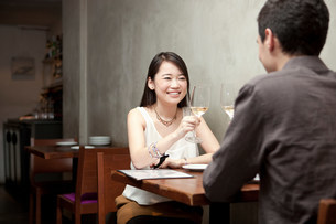 Young couple toasting white wine in restaurantの写真素材 [FYI03499309]