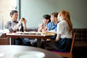 Four friends in restaurant, young man taking photoの写真素材 [FYI03499329]