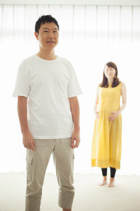 Man with pregnant woman in background, portraitの写真素材 [FYI03499393]