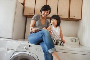 Mother and daughter sitting on washing machine using tabletの写真素材 [FYI03499452]