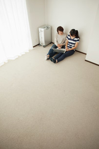 Mother and teenage daughter sitting on floor using laptopの写真素材 [FYI03499480]