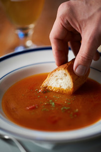 Hand dipping bread into bowl of tomato soupの写真素材 [FYI03499569]
