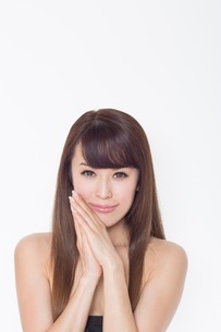 Portrait of brunette woman with hands on cheekの写真素材 [FYI03499667]
