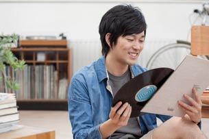 Portrait of young man holding vinyl recordの写真素材 [FYI03499751]