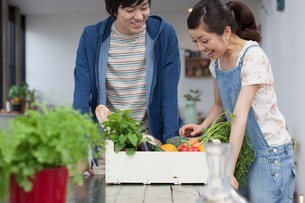 Young couple in kitchen with box of vegetablesの写真素材 [FYI03499764]