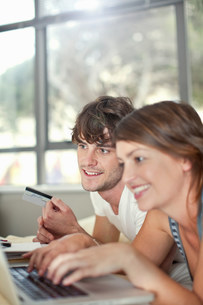 Young couple with laptop and credit cardの写真素材 [FYI03499865]