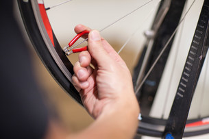 Close up of person using spoke wrench on bicycle wheelの写真素材 [FYI03500080]