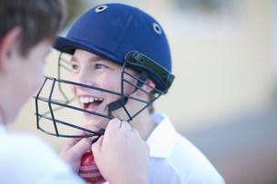 Boy putting cricket helmet on another boyの写真素材 [FYI03500132]