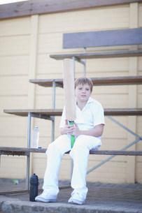 Boy holding cricket bat sitting on bleachersの写真素材 [FYI03500136]