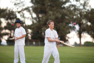 Boys practising hitting cricket ball with batの写真素材 [FYI03500152]