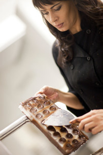 Woman with chocolate mould and palette knifeの写真素材 [FYI03500205]
