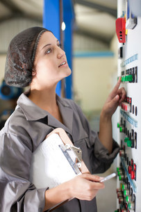 Woman at control panel in olive processing plantの写真素材 [FYI03500266]