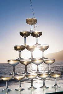 Champagne pouring into glasses with sea in backgroundの写真素材 [FYI03500328]