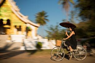 Woman riding bicycle with parasol, Luang Prabang, Laosの写真素材 [FYI03500411]