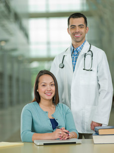 Mid adult doctor and young student smiling, portraitの写真素材 [FYI03500475]