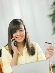 Young woman using credit card over the phone, portraitの写真素材 [FYI03500548]