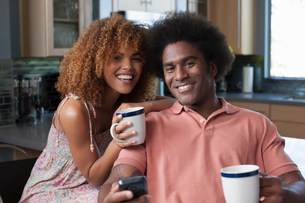 Mid adult woman and mature man holding coffee mugs, portraitの写真素材 [FYI03500632]