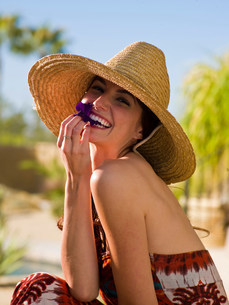 Young woman wearing sun hat and holding purple flower petal,の写真素材 [FYI03500711]