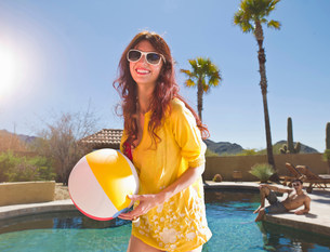 Young woman holding beach ball at poolside, portraitの写真素材 [FYI03500721]