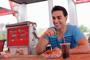 Young man eating onion rings in diner, smilingの写真素材 [FYI03500835]