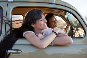 Young women travelling in car on road trip, smilingの写真素材 [FYI03500968]