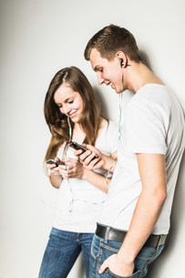 Teenage couple leaning against wall listening to mp3 playerの写真素材 [FYI03501063]