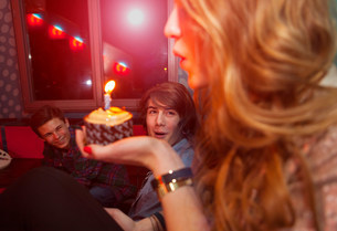 Teenage girl blowing out candle on birthday cakeの写真素材 [FYI03501174]