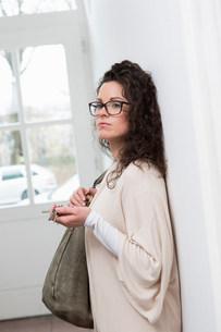 Woman leaning against wall in hallway holding keys and handbの写真素材 [FYI03501304]