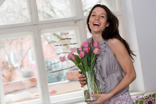 Mid adult woman holding vase of pink flowersの写真素材 [FYI03501332]