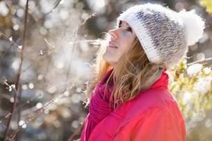 Young adult woman among snow-covered tree branchesの写真素材 [FYI03501366]