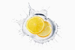 Two slices of lemon splashing in liquidの写真素材 [FYI03501380]