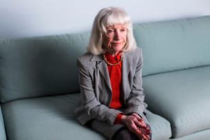 Senior woman sitting on sofa with blank expressionの写真素材 [FYI03501515]