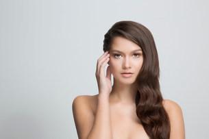 Portrait of brunette woman touching faceの写真素材 [FYI03501580]