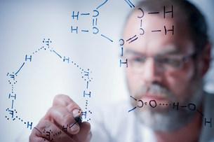Scientist writing scientific symbols on glassの写真素材 [FYI03501598]