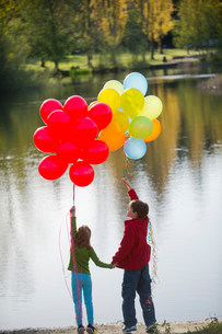 Brother and sister with bunches of balloons in parkの写真素材 [FYI03501833]